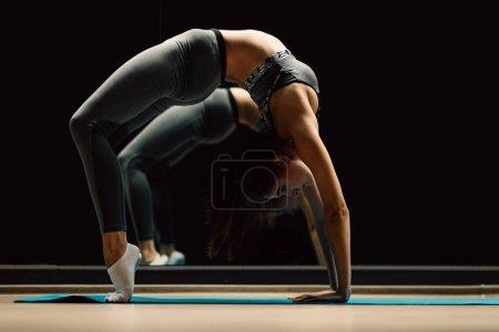 Photo pour Sportswoman sur l'étirement assis sur le tapis dans la salle de sport sur fond noir - image libre de droit
