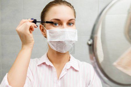 Photo pour Gros plan de blonde en médecine avec mascara et miroir dans la main à la salle de bain - image libre de droit