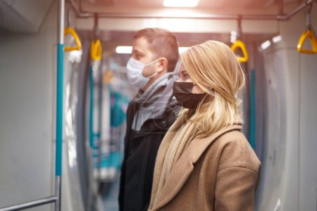 Photo for Side view of young man and woman in medical masks standing next to subway car. Coronavirus pandemic. - Royalty Free Image