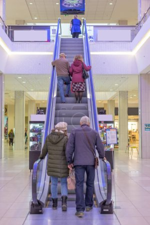 Escalator with people in a large shopping mall go ...