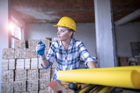 Photo pour Ingénieur civil portant un casque de sécurité jaune travaillant sur un plan intérieur dans une maison de rénovation - image libre de droit