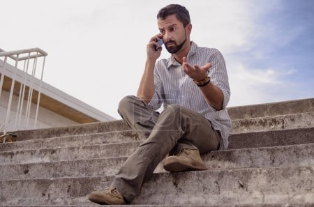 Photo for Young man sitting on the floor and talking on mobile phone - Royalty Free Image