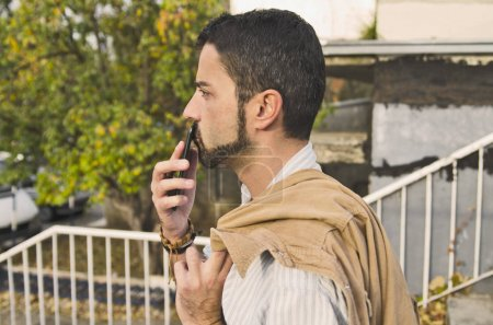 Photo pour Homme avec barbe fumer cigarette dans le parc - image libre de droit
