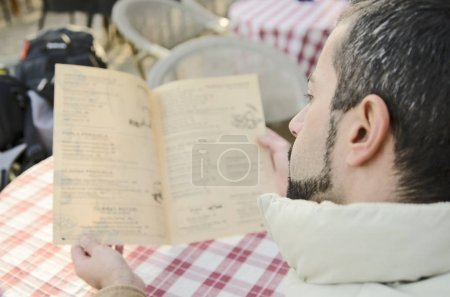 Photo for Young man reading book in bed - Royalty Free Image