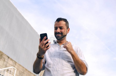 Photo for Handsome young man using mobile phone while standing outside - Royalty Free Image