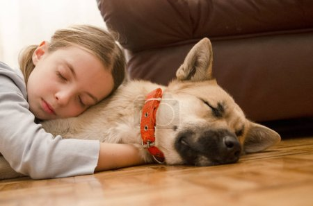 Photo for Cute little girl with dog lying on the floor - Royalty Free Image