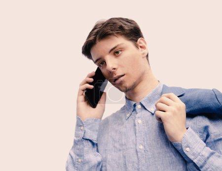 Photo pour Jeune homme parlant au téléphone - image libre de droit