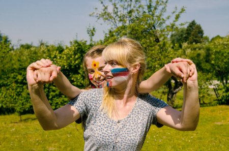Photo for Mother and daughter with paint on face have fun and play outdoor.Cheerful painted face young women and child girl.Carry little girl on the scabies. - Royalty Free Image