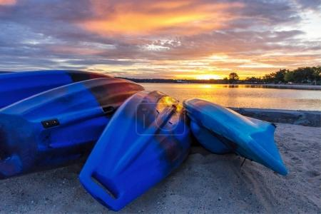 Summer Kayak Sunrise. Row of colorful Kayaks line the shore of a sandy beach as sunrise colors reflect in the calm waters of Lake Michigan. Traverse City, Michigan.