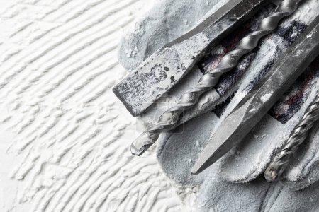 Photo pour Perceuse à marteaux avec gants sur une surface blanche - image libre de droit