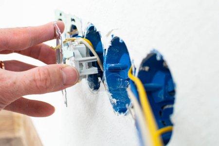 Photo pour Un électricien installe une prise de courant dans une maison neuve - image libre de droit