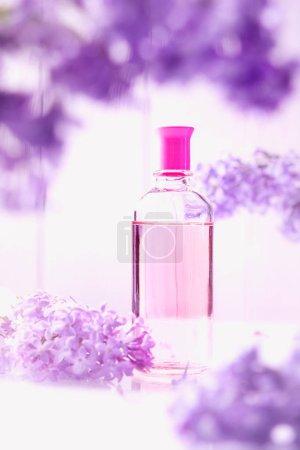 Photo pour Flacon de parfum rose avec fleurs lilas sur fond blanc - image libre de droit