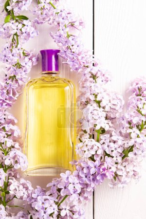 Photo pour Bouteille jaune de parfum féminin avec fleurs lilas sur fond blanc en bois - image libre de droit
