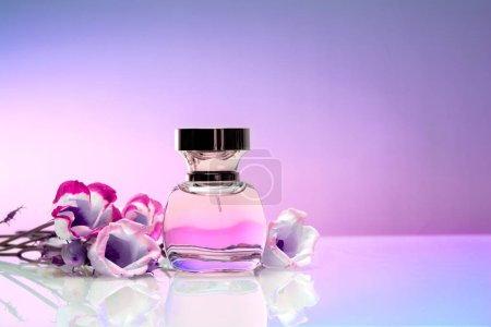 Photo pour Bouteille de parfum féminin avec fleurs sur fond coloré - image libre de droit