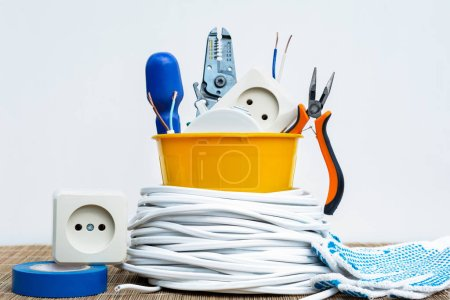 Photo for A set of an electrician in a yellow plastic pot and a wire spool - Royalty Free Image