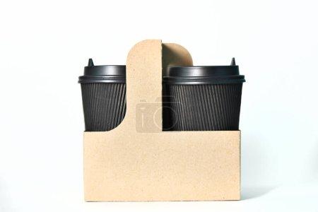 Photo pour Tasses de papier jetables de couleur noire dans le contenant Tasses de papier pour le café chaud. Du café pour aller. Tasse de papier pour le café. - image libre de droit