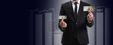 Photo pour L'homme d'affaires compare les dollars et le graphique montre une augmentation des bénéfices à l'avenir. Concept d'entreprise et croissance financière et crise en raison de la pandémie 2020 - image libre de droit