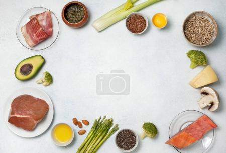 Photo for Ingredients for ketogenic diet: meat, bacon, fish, broccoli, asparagus, avocado, mushrooms, cheese, sunflower seeds, chia seeds, pumpkin seeds, flax seeds. view from above. copy space - Royalty Free Image