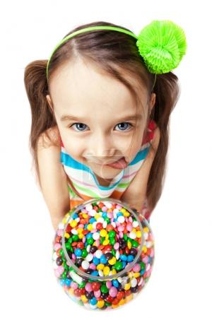 Funny child with candys licking her lips on a white background. Happy little girl with sweets.