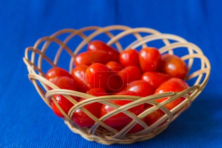 fresh tomatoes in a basket on a blue background