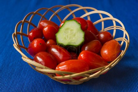 fresh tomatoes with cucumber in a basket on a blue background