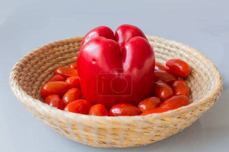 fresh tomatoes with red paprika in a basket