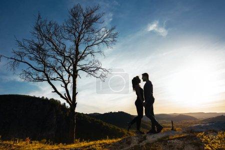 Photo pour Silhouette d'un couple amoureux. Un homme et une fille étreignant au coucher du soleil. Deux voyages. Amoureux de la nature. Homme et femme regardant le coucher du soleil. Amoureux au coucher du soleil. Voyage dans les montagnes. Voyage de lune de miel - image libre de droit