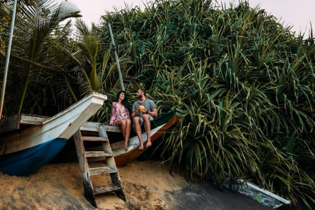 Foto de Viaje de luna de miel. Pareja enamorada en el coco de tomar el sol. Pareado en la orilla de la isla Paraíso. Hombre y mujer en Bali. Relájese en la isla. romance navideño. Viaje a Asia. Feliz pareja - Imagen libre de derechos