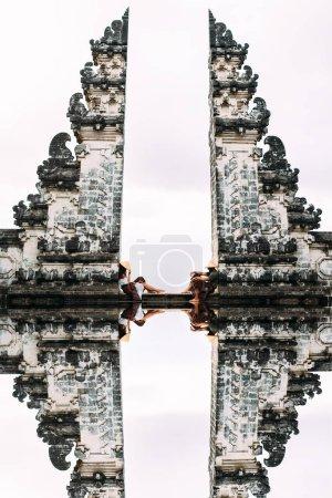 Photo pour Couple à la porte de Bali. Un homme et une femme voyageant sur l'île de Bali Indonésie. Le couple voyage dans le monde entier. Couple à la porte divisée de Candi Bentar. Homme et femme dans un temple balinais - image libre de droit