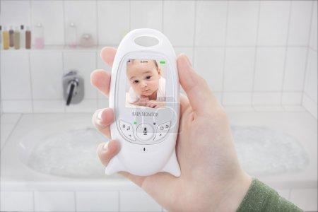 Photo pour Maman bébé contrôle via moniteur de bébé lorsque vous prenez un bain - image libre de droit