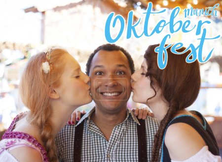 Young man getting kissed on the cheek by two german girls at Oktoberfest