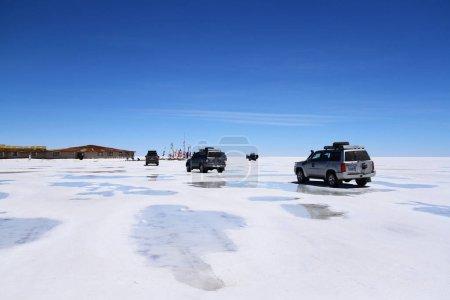 Foto de Vehículos todoterreno están en el crucero en las costras de sal de Uyuni Salt Flats, Bolivia - Imagen libre de derechos