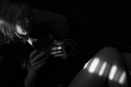 Foto de Mujeres jóvenes deprimidas sentadas en el suelo en una habitación oscura y usando su teléfono móvil. Fotografía en blanco y negro. Espacio de texto. - Imagen libre de derechos