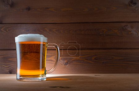Photo for Glass of golden beer on wood background - Royalty Free Image