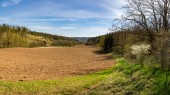 Plowed field, forest and blue sky with clouds