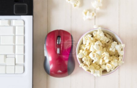 Popcorn with computer on wooden background, shallow focus.