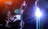 Industrial worker Welding and bright sparks. Hard job