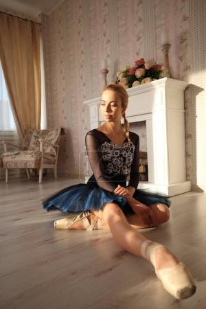 Photo pour Portrait d'un danseur de ballet professionnel assis sur le sol en bois - image libre de droit