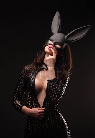 Photo pour Femme sexy avec des gros seins portant un permanent de masque de lapin noir sur fond foncé - image libre de droit
