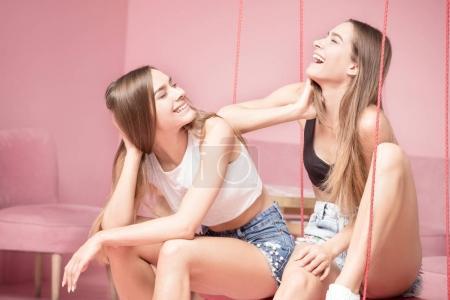 Photo pour Le sourire est toujours bon. Du temps en famille, deux belles jumelles heureuses riant ensemble. Les filles parlent, s'amusent. Fond rose . - image libre de droit