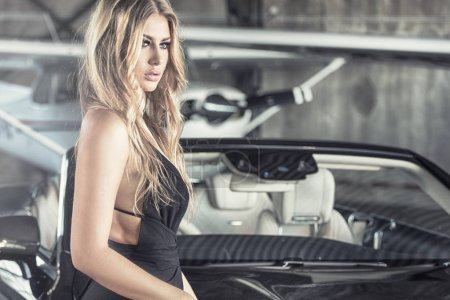 Photo pour Elegant blonde beautiful woman standing by luxury car and small aeroplane. Girl wearing black dress. - image libre de droit