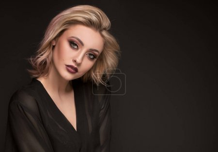 Photo pour Sensual delicate blonde lady with glamour makeup posing in elegant style, looking at camera. Studio shot, dark background. Caucasian sexy woman. - image libre de droit