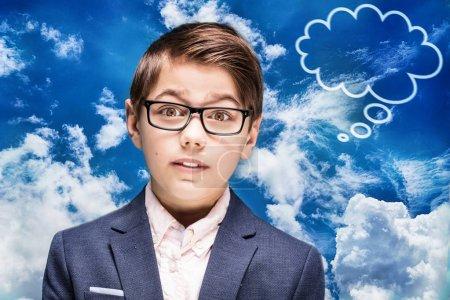 Smart boy in eyeglasses thinking.