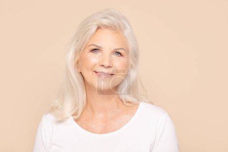 Photo pour Une belle femme âgée souriante regardant la caméra. Beige studio boulangerie. Beaucoup d'espace de copie. - image libre de droit