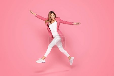 Photo for Cheerful young crazy woman jumping over pastel pink background in studio. People lifestyle concept. - Royalty Free Image