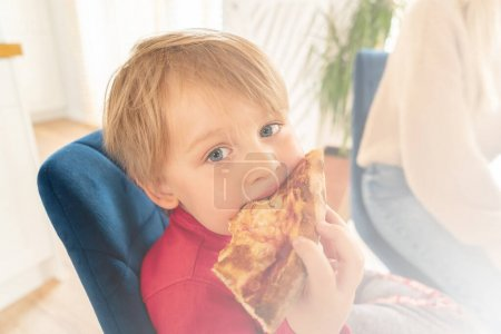 Photo for Cute blonde boy eating slice of pizza at fast food restaurant. Hungry kid. Child unhealthy meal concept. - Royalty Free Image
