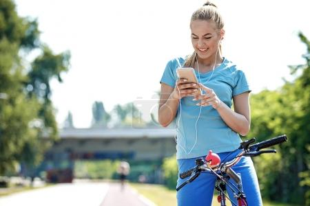 Photo for Young blonde woman is riding bike and listening music. - Royalty Free Image