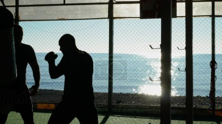 Photo for Silhouettes. Two male boxer athlete are training in an outdoor gym on a beach near the sea - Royalty Free Image