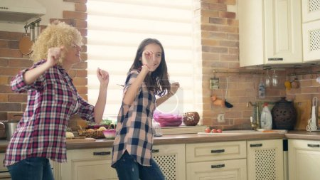 Photo for Dancing with mom. Cute teen daughter dancing in the kitchen with her loving mother. - Royalty Free Image