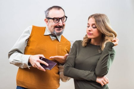 Nerdy man showing his wealth to a beautiful woman